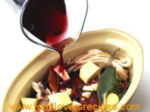 Red wine being poured over venison, butter, bacon, herbs and spices in casserole dish